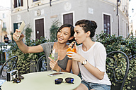 Italy, Padua, two young women taking selfie at sidewalk cafe - ALBF00073