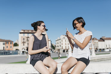 Italy, Padua, young woman taking picture of her friend with smartphone - ALBF00094