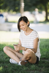 Smiling young woman sitting on a meadow listening music with earphones - ALBF00106