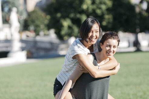 Young woman giving her friend a piggyback ride in the park - ALBF00109