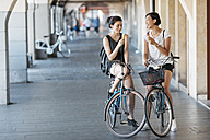 Two young women with bicycles eating icecream - ALBF00118