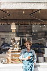 Coffee roaster holding cup in front of his his shop - KNSF00877
