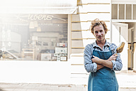 Portrait of confident coffee roaster in front of his his shop - KNSF00886