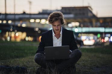 Businessman sitting on meadow at dusk using laptop - KNSF00889