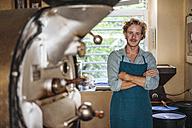 Portrait of confident coffee roaster in his shop - KNSF00892