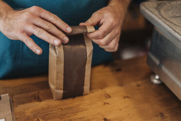 Close-up of man packing bag of coffee at shop counter - KNSF00910