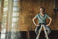 Man sitting on stepladder in unfinished room - KNSF00925