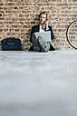 Businessman sitting on floor using laptop and cell phone - KNSF00931