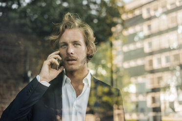 Businessman on cell phone behind windowpane - KNSF00940