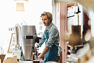 Portrait of coffee roaster at counter in his shop - KNSF00949
