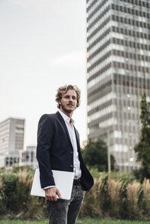 Businessman holding laptop outdoors - KNSF00982