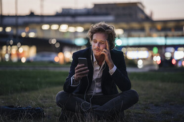 Businessman sitting on meadow at dusk with cell phone and earphones - KNSF00988