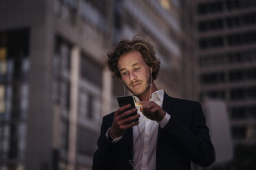Businessman in the city at dusk using cell phone - KNSF00991