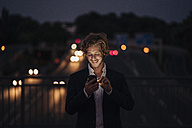 Businessman on a bridge at night using cell phone - KNSF00994