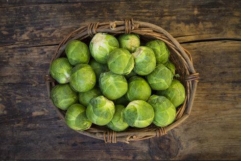 Wickerbasket of Brussels sprouts on dark wood - LVF05835