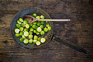 Frying pan with Brussels sprouts and cooking spoon on dark wood - LVF05841