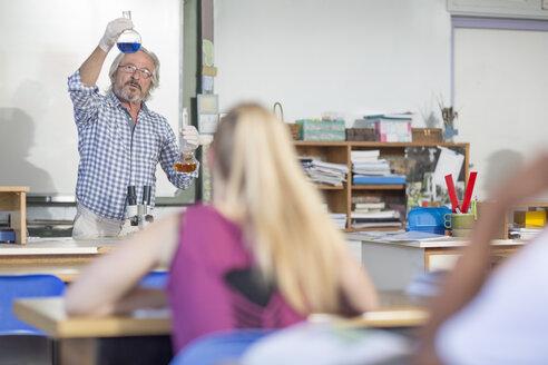 Science teacher in class holding flasks - ZEF12641