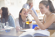 Happy teenage girls in high school chemistry class experimenting - ZEF12644