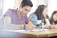 Science student working in class with microscope - ZEF12647
