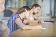 Female students writing during class test - ZEF12662