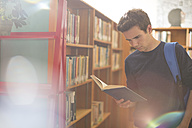 High school student reading a book in library - ZEF12668