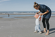 Netherlands, Schiermonnikoog, mother walking with little daughter on the beach - DWF00261