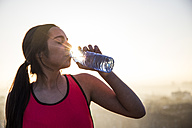 Female athlete drinking water at sunset - ABZF01846