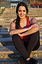Smiling female athlete sitting on stairs - ABZF01849