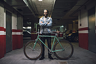 Young man with his fixie bike in a garage - RAEF01716