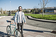 Young man walking with his fixie bike in a park - RAEF01719