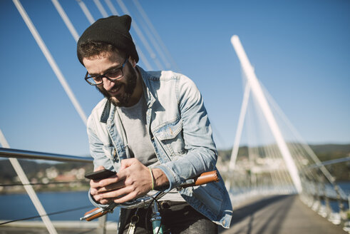 Smiling young man with fixie bike using a smartphone on a bridge - RAEF01728
