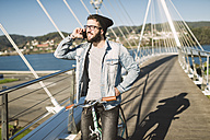 Young man with fixie bike on a bridge on the phone - RAEF01731