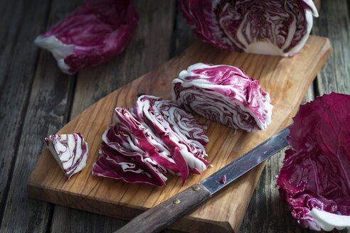 Sliced radicchio and kitchen knife on wooden board - YFF00632