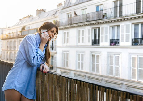 Young woman standing on balcony talking on the phone - MGOF02866