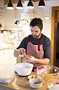 Man standing in kitchen, preparing cake dough - HAPF01328