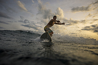 Indonesia, Bali, surfer at sunset - KNTF00629