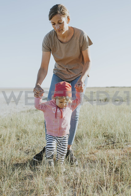 Netherlands, Schiermonnikoog, mother walking with little daughter on a meadow - DWF00270