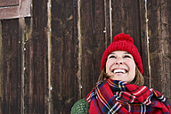 Portrait of smiling woman wearing red bobble hat in winter looking up - FSF00737