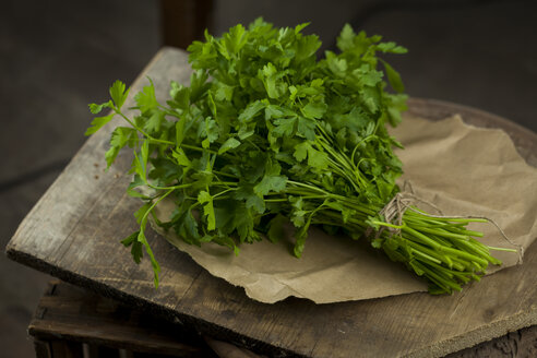 Bunch of flat leaf parsley on brown paper and wood - JUNF00818