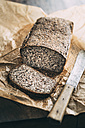 Home-baked wholemeal gluten-ree bread and bread knife on brown paper - IPF00353