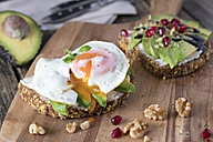 Protein bread slice with cream cheese, sliced avocado and fried egg on wooden board - YFF00637
