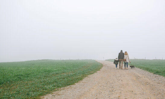 Family walking with dog on a path on a foggy winter day - DAPF00552
