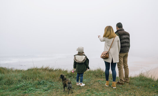 Family with dog at the coast on a foggy winter day looking at view - DAPF00555