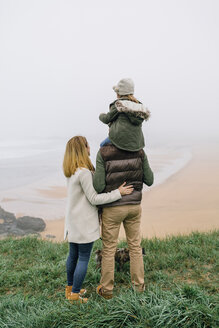 Family with dog at the coast on a foggy winter day looking at view - DAPF00558