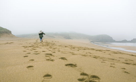 Girl running on the beach on a foggy winter day - DAPF00564
