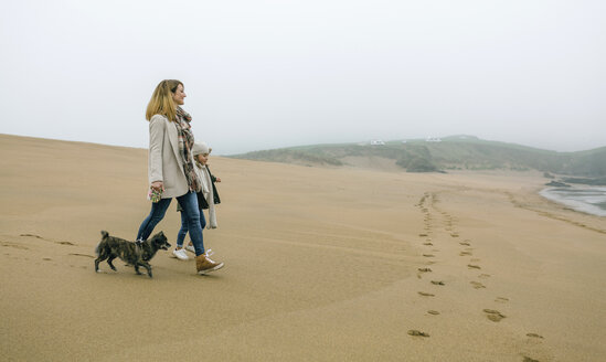 Woman walking with daughter and dog on the beach on a foggy winter day - DAPF00567