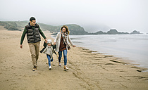 Happy family with daughter walking on the beach in winter - DAPF00570