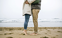 Low section of couple standing barefoot on the beach - DAPF00585
