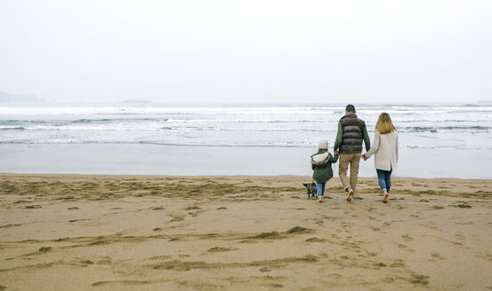 Family walking with dog on the beach in winter - DAPF00588