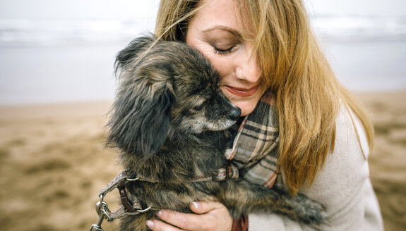 Woman hugging her dog on the beach in winter - DAPF00591